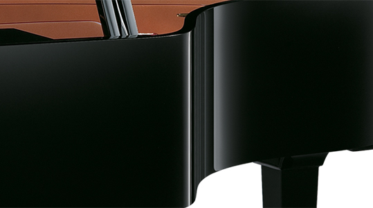 close of up grand piano side, showing fine-furniture finish